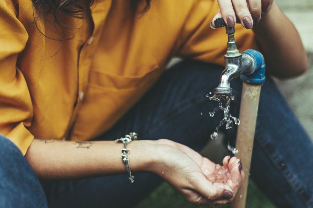 woman getting water from an outdoor faucet