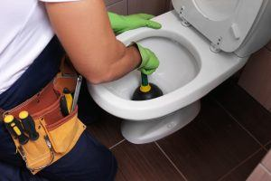 plumber plunging a clogged toilet