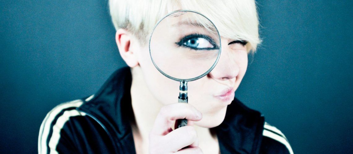 woman with magnifying glass to represent examing the facts and fiction of septic tanks